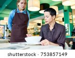 Small photo of Portrait of elegant woman complaining about food quality and taste to young waitress in cafe