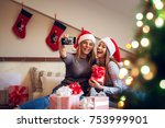Small photo of Two adorable excited girlfriends with Santa hat sitting on the bed for Christmas holidays one next to another and taking a selfie while laughing on laud.
