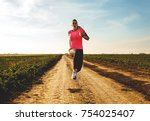 athletic woman running on rural ... | Shutterstock . vector #754025407