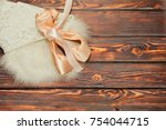 Small photo of Pair of traditional silk new ballet shoes - pointes - lie on white swan props skirt on wooden lackered surface. Behind the theater stage concept. Top view, place for text.