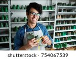 smiling young shoe repairman... | Shutterstock . vector #754067539