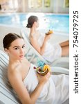 Small photo of Restful girl wrapped in towel holding tropical cocktail during rest