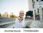 mature woman sitting outdoors... | Shutterstock . vector #754084684