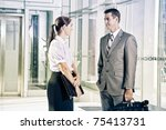 Businesswoman and Businessman talking in foyer in corporate building - stock photo