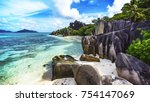 Stock photo turquoise water granite rocks and palm trees in the white sand of anse source d argent on the 754147069