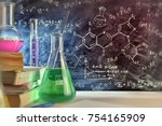 Small photo of Classroom desk and drawn blackboard of chemistry teaching with books and instruments. Chemical sciences education concept. Horizontal composition. Front view