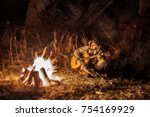 Small photo of Armed rebel resting by the fire and playing the guitar, grained photo