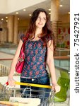 Beautiful woman at a shopping center with basket - stock photo