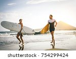 young couple of surfers running ... | Shutterstock . vector #754299424