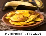 Small photo of Fried slices of ripe plantains, traditional and popular snack and accompaniment in Central and Northern South America, photographed with natural light (Selective Focus on the front of the top slice)