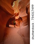 Small photo of Man with backpack walking down the slot canyon in Navajo Reservation. Hiker in the bottom of slot canyon. Orange and red curvy cliffs. Man enjoying a solitude in colorful chamber.