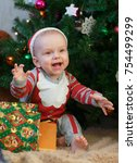 Small photo of A cheerful little boy in a red cap and new-year suit laughing all the way with his hands diluted in the sides, sitting on a soft blanket among the presents on the background of the Christmas tree.