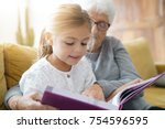 little girl reading book with... | Shutterstock . vector #754596595