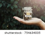 Small photo of Hand holding glass jar with coins with SAVE label on green leaves background. Money saving for house, dream, vacation. Economic crisis and financial stability concept