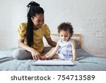 cute baby girl sitting on bed... | Shutterstock . vector #754713589