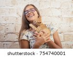 Stock photo girl with a favorite kitten young beautiful girl is holding a red kitten lovely portrait of a 754740001