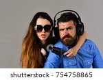 Small photo of Couple in love wears headphones and holds microphone. Man with beard and girl hug on grey background. Pleasure, music and creative lifestyle concept. Music fans with concentrated faces wear sunglasses