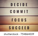 Small photo of Motivational and inspirational quotes - Decide, commit, focus, succeed. With blurred vintage styled of wooden background.