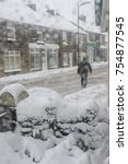 Small photo of WREXHAM, UK - MARCH 22, 2013: Man walking though heavy snowfall along a Welsh High Street. The worst snow storm in many years caused much damage across the country. Vertical.