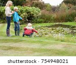 mother and sons near pond | Shutterstock . vector #754948021
