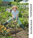 Small photo of A young girl in a allotment garden