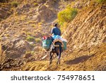 Moroccan villager using a donkey to carry out the tourist luggage across the Atlas mountains, Morocco.