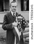 Small photo of President Calvin Coolidge holding an American flag. May 2, 1924.