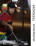 Small photo of PERAK, MALAYSIA - OCTOBER 1st, 2016: A man frying meal at the street stall at night at Sri Iskandar, Perak.