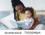 Beautiful African woman sitting on bed and reading a book to her cute baby daughter.