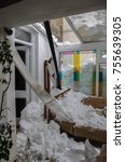 Small photo of Snow damage inside a home after thick icy snow slid of a roof and crashed through a conservatory.