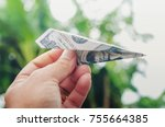 Small photo of Business grow concept Hand holding rocket money paper airplay folding with dollar symbol Expect the future positive thinking meaningful ambitious optimistic thinking trust success self belief Decide