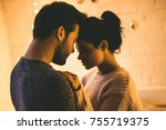 Small photo of Passionate romantic couple in sweaters are spending time together before New Year at home. Tender couple hugging on the background of shiny garland.