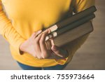 Small photo of Hands of female student in yellow sweater carrying books in a library to study her class assignment research - education concept