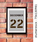 Small photo of DECEMBER 22th. 22 DECEMBER calendar on the wood photo frame with brown brick background. Winter season.