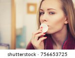 Small photo of Skin complexion care concept. Young woman using cotton pad to remove make up or dirt from face.