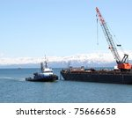 A tug boat pulling into an industrial shipping yard with a crane in Alaska with a bright blue sky - stock photo