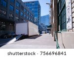 Semi Truck for delivery of goods in the city limit with a lowered gangway standing near the warehouse on the city street for loading or unloading goods for starting delivering - stock photo