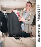 Small photo of Adult male in shirt measuring business clothes jacket in the store