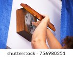 Small photo of old woman winds the old wall clock with the key. The symbol of the passage of time and the alternation of generations.
