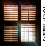 Small photo of Shuttered window with one pane open letting through rays of light and a faint image of autumn leaves outside