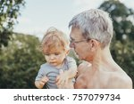 Stock photo baby girl with her grandfather in the garden 757079734