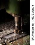 Small photo of The working process The old milling machine processes the part. There is a dural shaving around it.