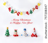 "Christmas greeting card with hanging banner and cute wooden figurine of Christmas tree, present, Snowman and Santa Claus isolated on white background. Wording ""Merry Christmas & Happy New Year"""