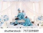 Small photo of Portrait of playful couple sitting on bridal dais decoration.