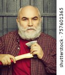 Small photo of Senior man. Old man shaving white beard with axe on wooden background