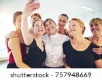 Small photo of Mixed age group of laughing women standing arm in arm together taking a selfie during ballet class