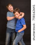 Small photo of Brothers having fun whilst posing. Boys portrait, young little cute and adorable kids, little obstreperous scamps. Poses, face expressions, ease, black background.