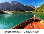 Wooden boat on a beautiful alpine lake; prow on foreground and mountain range on background. Photo taken in Braies Lake (Dolomites, Italy).