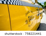 Small photo of Side view of a shining yellow classic taxi with black and white grid displaying ride fare, New York, USA