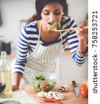 young woman eating fresh salad... | Shutterstock . vector #758253721